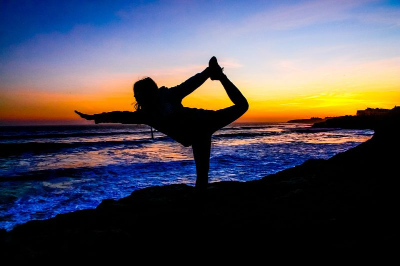 woman in yoga pose at sunset on beach