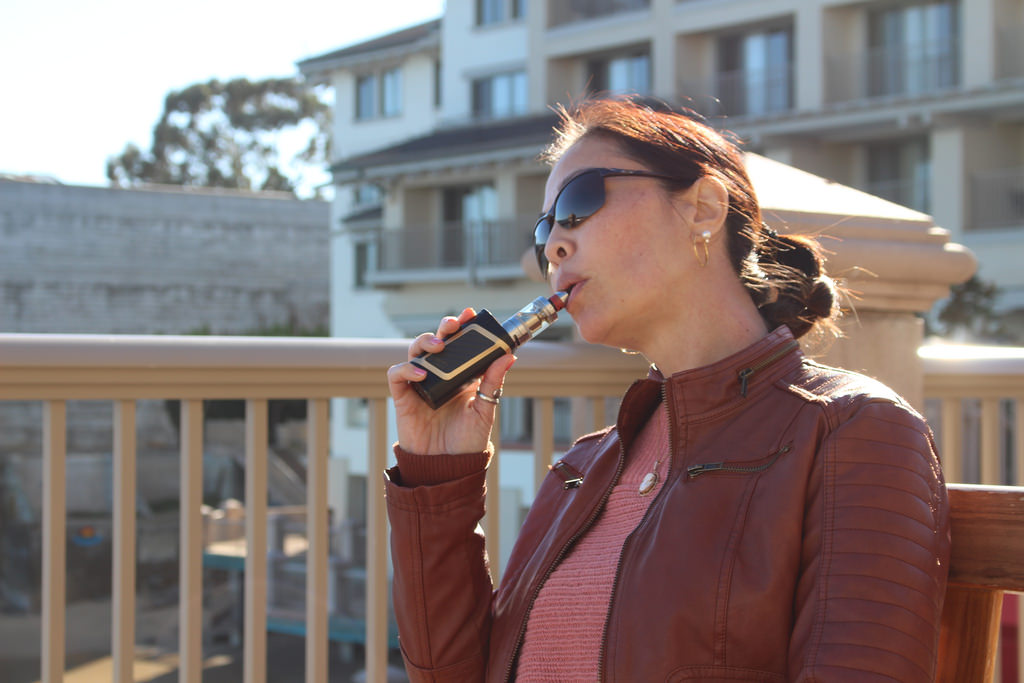 woman using a portable vaporizer