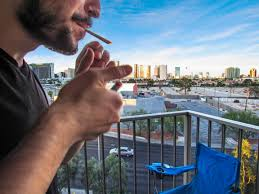 man smoking a cannabis joint on a balcony