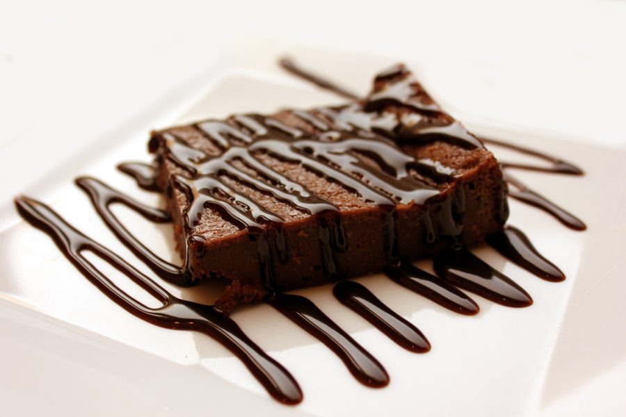 brownie on white plate drizzled with chocolate icing