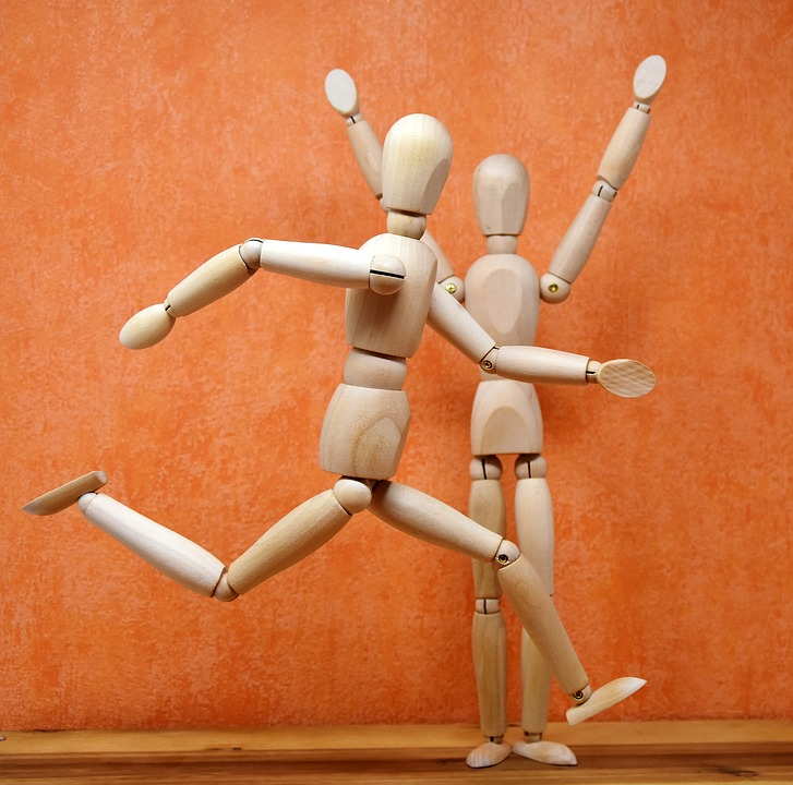 wooden jointed dolls in positions of running